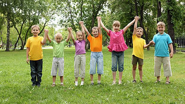 Eine Gruppe von Kindern steht auf einer Wiese in einer Reihe, sie strecken die Hände in die Luft.