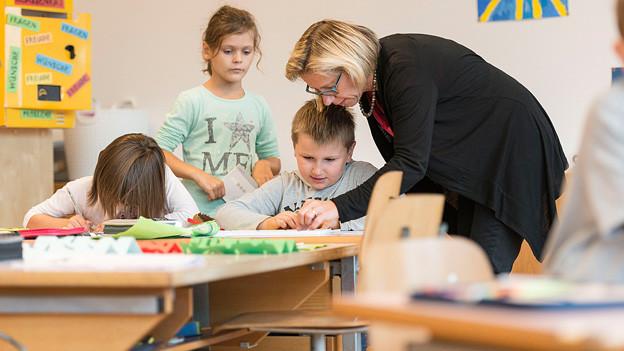 Eine Lehrerin mit Schülern im Klassenzimmer.