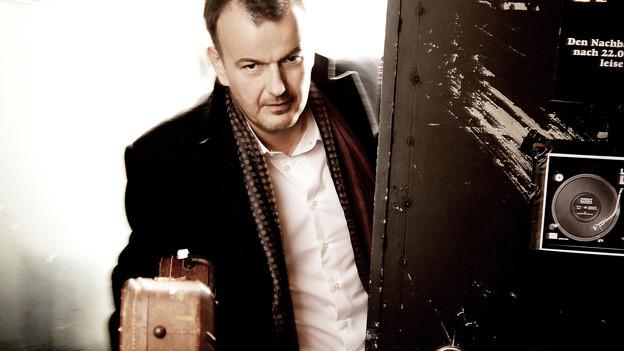 Porträt von Philipp Fankhauser mit dem Gitarrenkasten in der Hand.