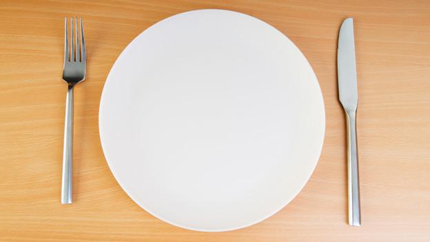 Weisser Teller und Besteck auf einem Holztisch.