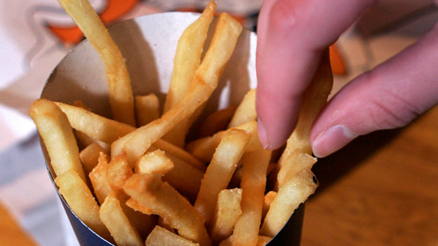 Imbiss-Pommes Frites mit Fingern essen.
