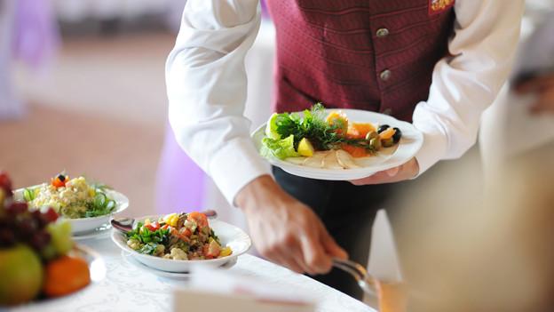 Kellner bringt einen Teller mit Essen.