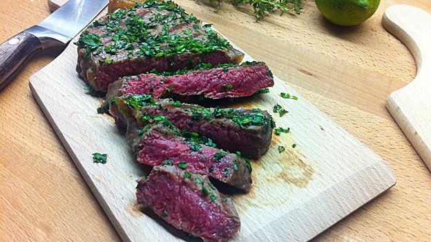 Ein stück Fleisch in frischen Kräutern gewendet.