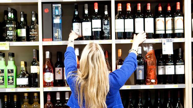 Eine Frau vor dem Weinregal.
