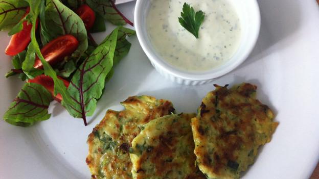 Ein weisser Teller mit Zucchetti-«Tätschli», einer kleinen Schale mit Sauerrahm-Dip und Salat.
