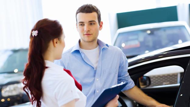 Ein Mann und eine Frau stehen bei einem Auto.