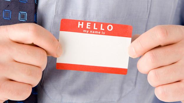 Ein Mann hält sich einen Aufkleber mit der Aufschrift «Hello, my name is» vor die Brust.