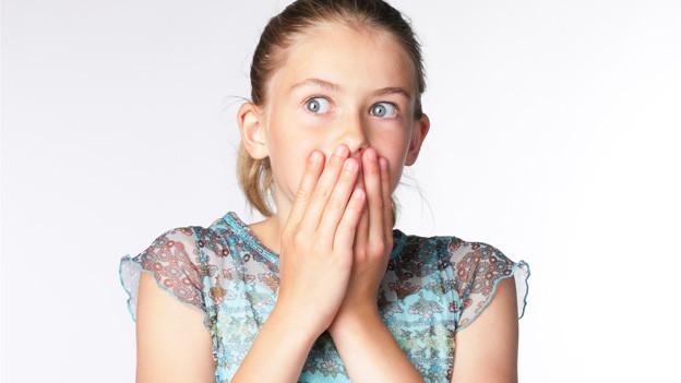 Ein Mädchen hält sich die Hände vor den Mund.