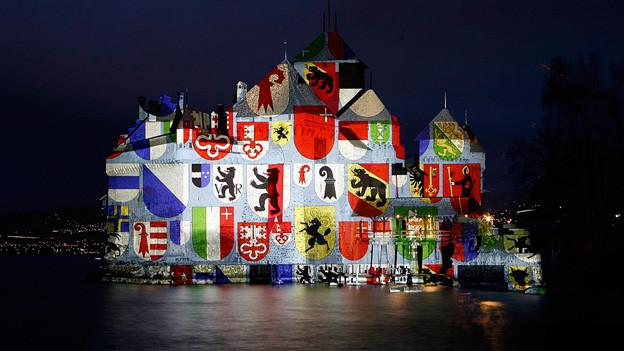 Lichtshow mit Schweizer Kantonswappen auf dem Schloss Chillon.