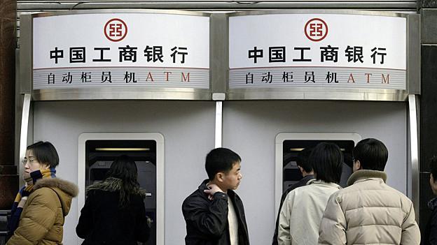 Chinesen vor Bankautomat.