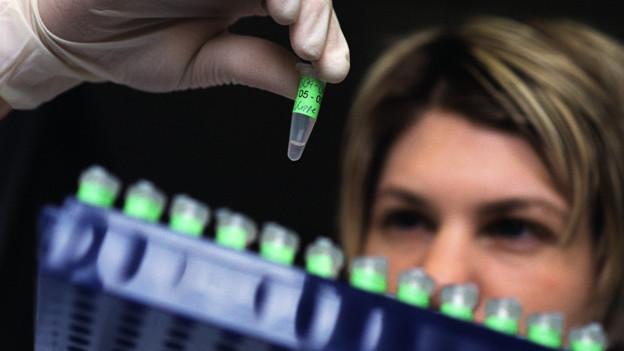 Frau betrachtet ein Fläschchen mit Flüssigkeit für die DNA-Analys.
