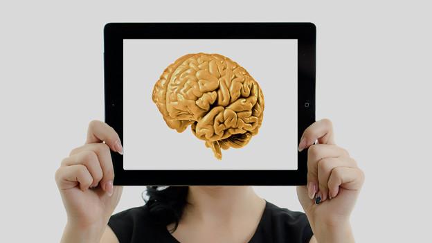 Eine Frau hält ein I-Pad vors Gesicht, auf dem ein Bild von einem Gehirn gezeigt wird.