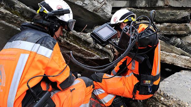 Zwei Mitglieder der Schweizerischen Rettungskette im Einsatz in Asphalttrümmern.