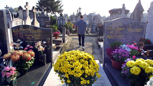 Ein junger Mann ist auf dem Weg eines Friedhofs unterwegs.