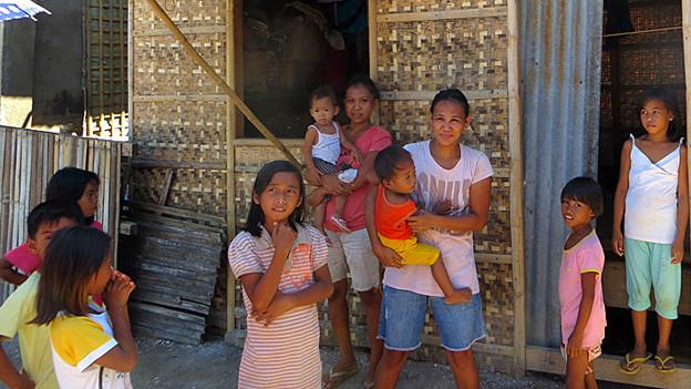 Philippinische Frauen und Kinder vor einem Haus.