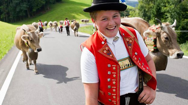 Ein junger Senn in Appenzeller-Tracht, im Hintergrund Kühe.