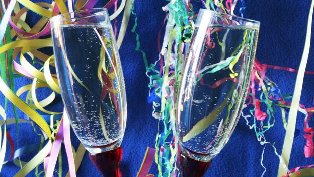 Zwei Champagnergläser, im Hintergrund Girlanden.