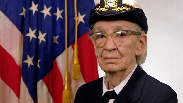 Admiral Grace Hopper in Uniform vor der USA-Flagge.