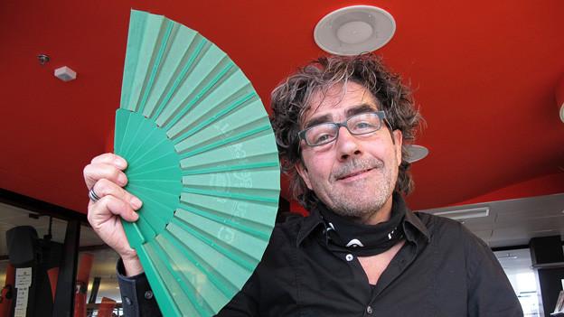 Thomas «Baldrian» Leuenberger mit einem Fächer im Radiostudio.
