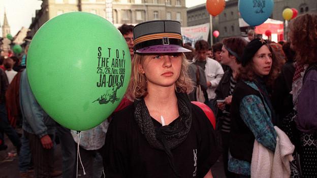 Mädchen mit Militärhut und grünem Ballon an der Kundgebung.