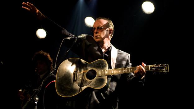 Tom Russell auf der Bühne mit Gitarre in der Hand.