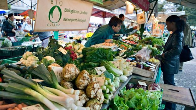 Kundin steht am Marktstand mit Biogemüse.
