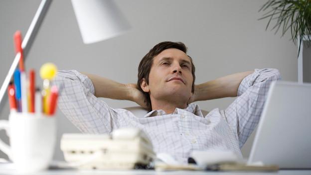 Ein Mann entspannt sich am Aarbeitstisch, indem er die Hände hinter den Kopf liegt.