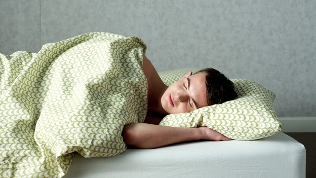 Ein Mann liegt schlafend im Bett.