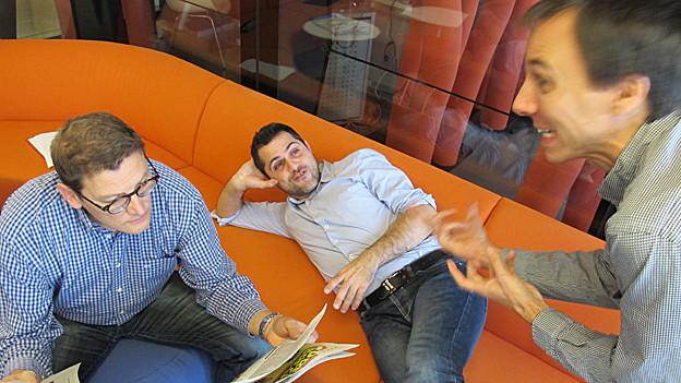 Die drei Redaktionskollegen aus den anderen Sprachregionen Zeitung lesend, gestikulierend und ruhend.