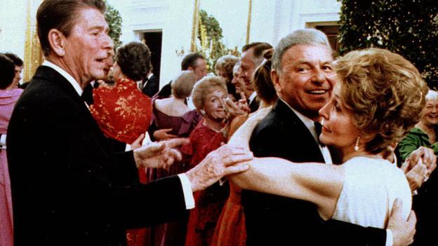 Ein Ball im Weissen Haus, Frank Sinatra und Nancy Reagan tanzen, Ronald Reagan steht daneben und legt seiner Frau die Hand auf den Arm.