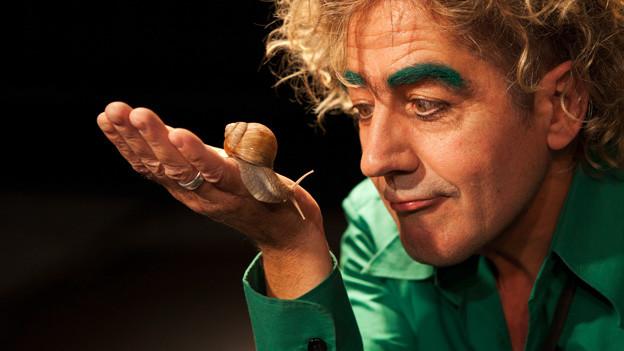 Thomas «Baldrian» Leuenberger mit einerSchnecke auf der Bühne.