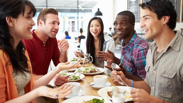 Internationale Menschen am Tisch.