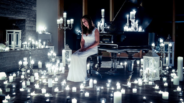 Eliane Müller sitzt in weissem Kleid an einem Flügel. Sie ist umgeben von ganz viel weissen Kerzen.