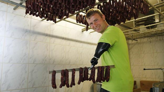 Bild von Wisi Zgraggen, der eine Stange hält, an der viele Würste hängen.
