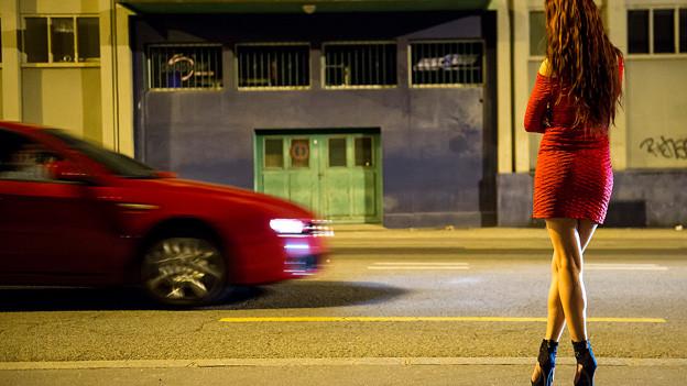 Eine Prostituierte in einem roten Kleid wartet am Strassenrand, ein rotes Auto fährt vorbei.