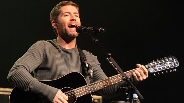 Josh Turner mit Gitarre auf der Bühne singend.