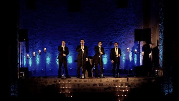Vier Männer auf der Bühne.