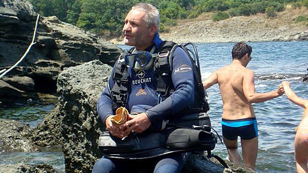 Thomas Gallati im Tauchanzug auf einem Felsen sitzend.