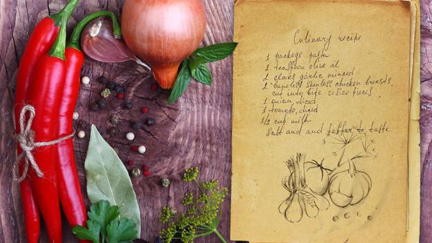 Gemüse und Rezept-Zettel auf einem Holzbrett.