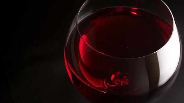 Ein Weinglas mit Rotwein drin.