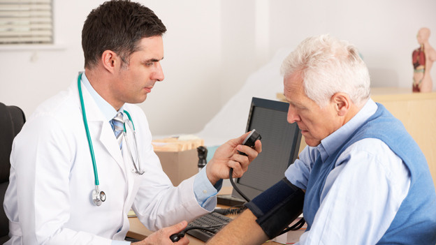 Arzt misst bei einem Patienten den Blutdruck.