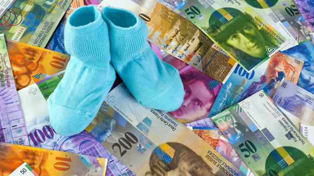 Babysocken auf Geldhaufen.