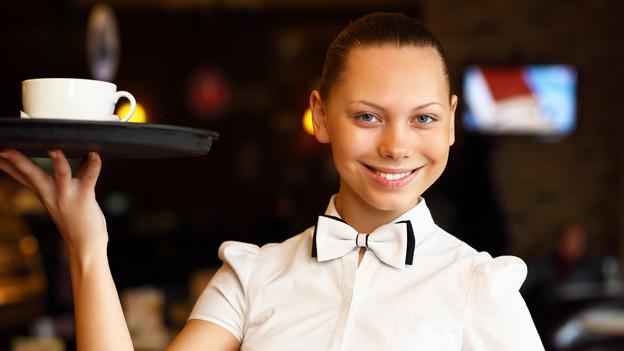 Eine Kellnerin trägt eine Tasse auf einem Tablett.