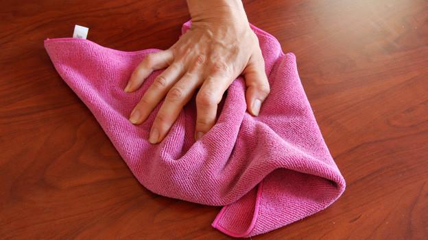 Eine Frauenhand mit Lappen auf einem Holztisch.