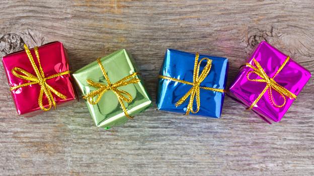Vier farbige Geschenke auf einem Holztisch.