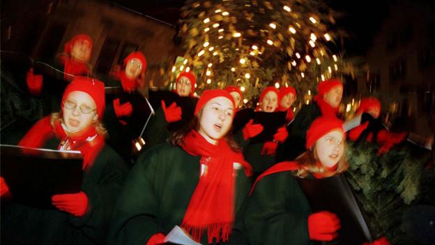 Kinder in roten Kappen und Schals am Singen unter einem Weihnachtsbaum.