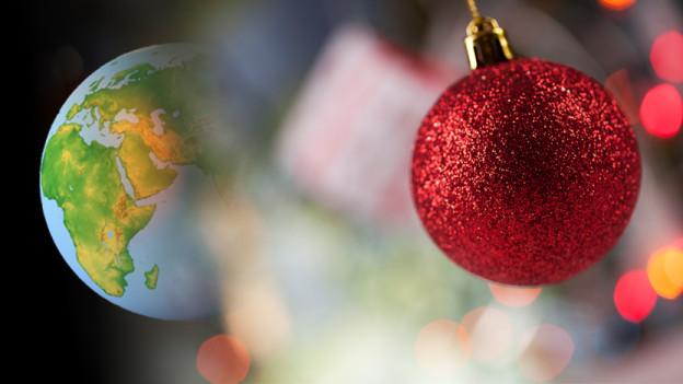 Rote Weihnachtskugel und Globus im Hintergrund.