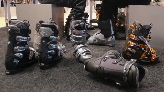 Im Laden liegen verschiedene Skischuhe am Boden. Hinten wird ein Kunde bei der Anprobe bedient.