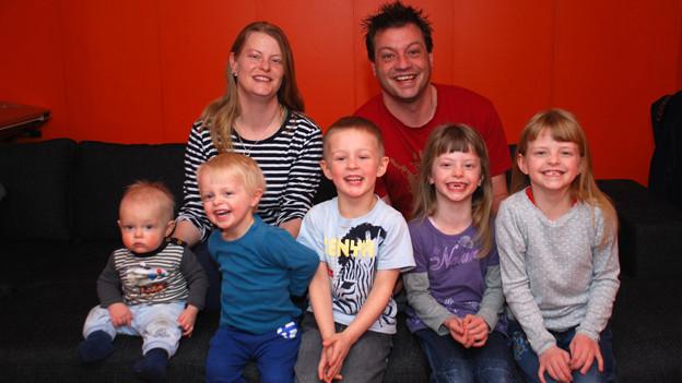 Michael Reinhard mit seiner Frau Edith und seinen fünf Kindern auf dem Sofa sitzend.