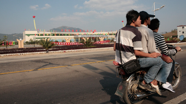 Drei Chinesen fahren auf einem Motorrad an einer Fabrik vorbei.